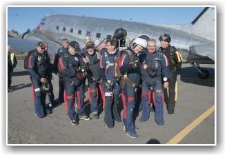 FARGEKLATTER: 12 glade fjes klare til å fargelegge Dakotaens dag fra himmelen. Veteranenes fallskjermklubb stilte med 12 mann, og bredest smiler Per Kulsrud (midt på bildet) som er akkurat like gammel som Dakotaen. FOTO: Martin Nilsen