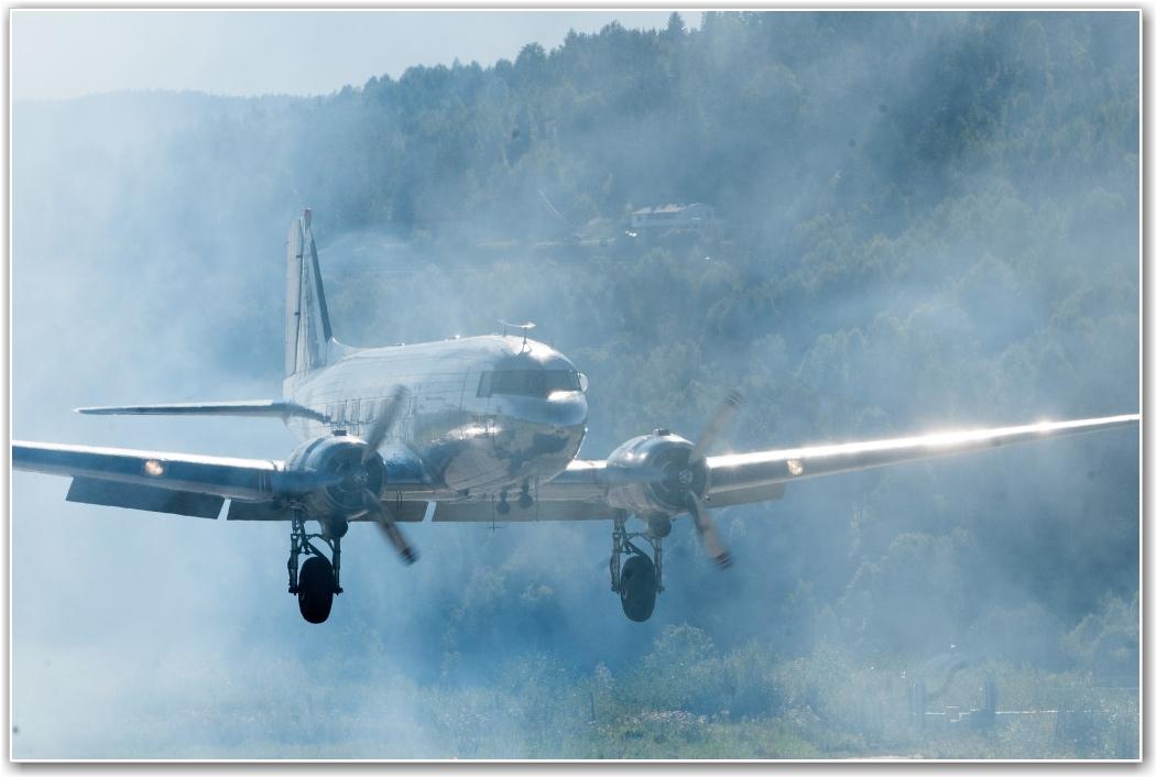 GUTTA I RØYKEN: Telemark Airshow ble åpnet med Veteranenes Fallskjermklubbs utsprang fra Dakotaen. Den landet like etter Jacob Holländers forrykende (!) acro-show, og derfor ser det ut som om Dak-en her kommer rett ut av tåkehavet. FOTO: Martin Nilsen