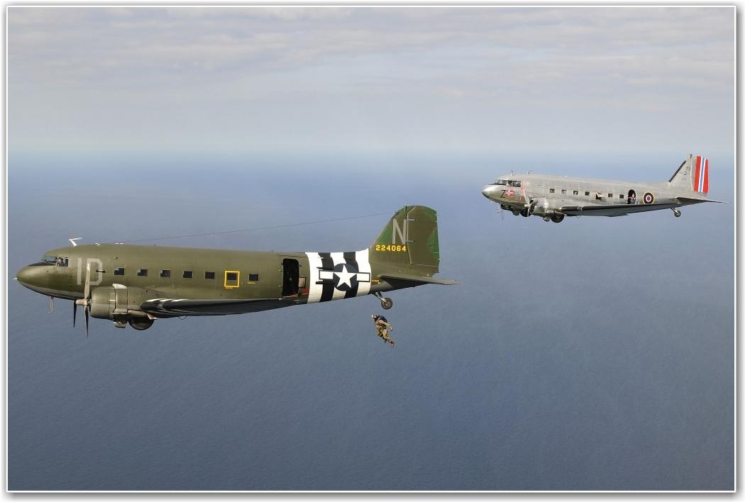 FORMASJONSHOPP: Dakota Norways DC 3 over Utah Beach i Normandie 6. juni, i formasjon med en amerikansk maskin som setter ut en hopper, mens hoppere er klar i døren på det norske flyet. FOTO: Dietmar Schreiber/ air2aircrew.com.