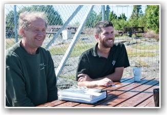 ERFARING PÅ BOK: Clive Edwards (t.v.) og Gordon Gray slapper av etter endt jobb på Torp og viser oss scarp-boken med noen  av arbeidene de har gjort med veteranfly over hele verden - en imponerende samling av erfaring som kom oss til gode denne gangen. FOTO: Martin Nilsen